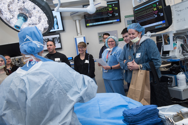 A clinician in a simulated operating room describes spinal fusion surgery for a group of patients and their families.
