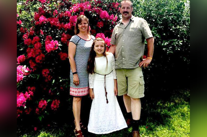 Maria poses with her parents in front of a bright flowering bush.