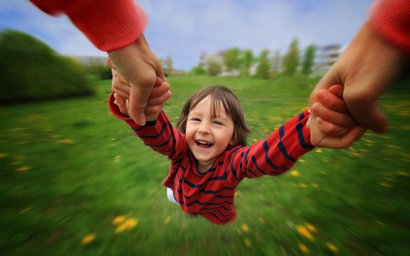 A child being swung in a field by a parent, as the ground spins