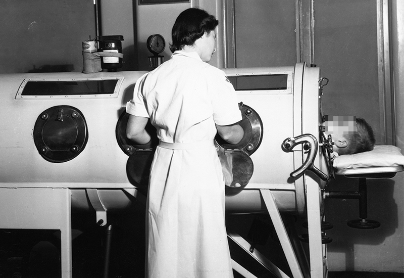 A physical therapist cares for a young boy in an iron lung