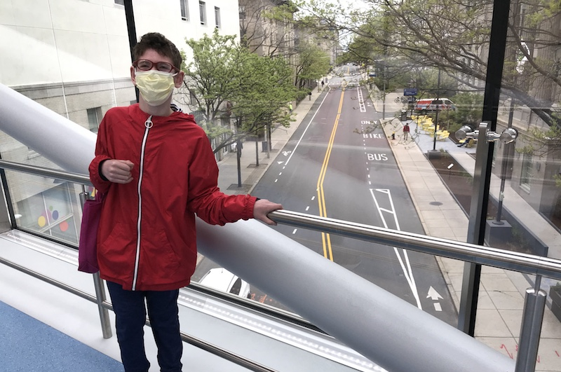 Jared, who has scoliosis, in a red jacket on the Boston Children's skybridge overlooking an empty street.