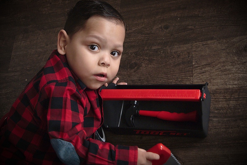 Gabby, who has short bowel syndrome, holds a saw from a play tool set. He is wearing a red plaid shirt.
