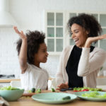 A mother and her child give each other a high five as they prepare food in the kitchen