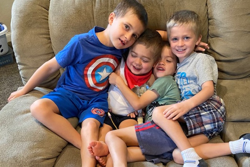 Joshy, who had a kidney transplant, plays on the couch with his three older brothers.