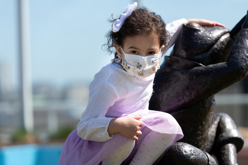 Laila, who has trichohepatoenteric syndrome, poses by a sculpture on the boston children's roof garden