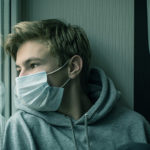 teen boy wearing a mask to suggest he has post-covid symptoms