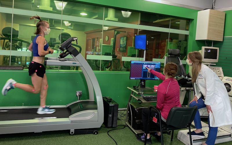 An athlete runs on a force-plate treadmill while sports medicine specialists review gait analysis data on a computer.