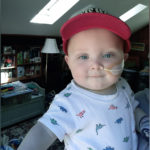 a photo of baby miles with an NG tube in his nose. he is wearing a red hat